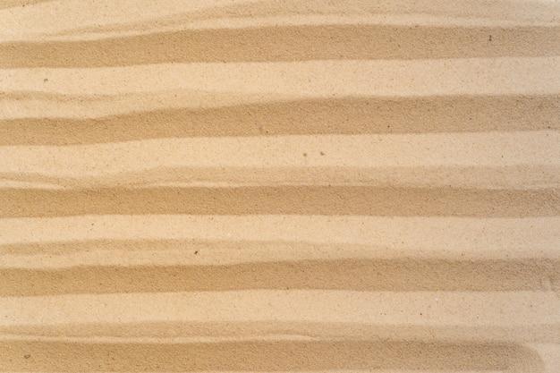 Предпосылка пляжа песка и картина текстуры с космосом.