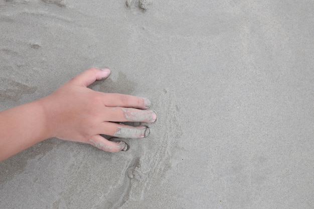 Sand on the beach and child's hand.