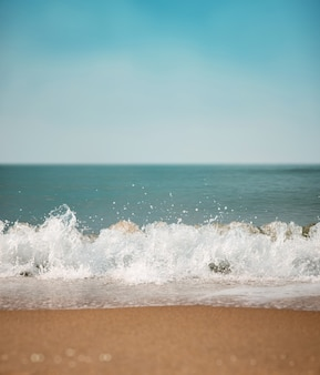 Sand beach and hard wave on summer sunny day. blue ocean and sky as background
