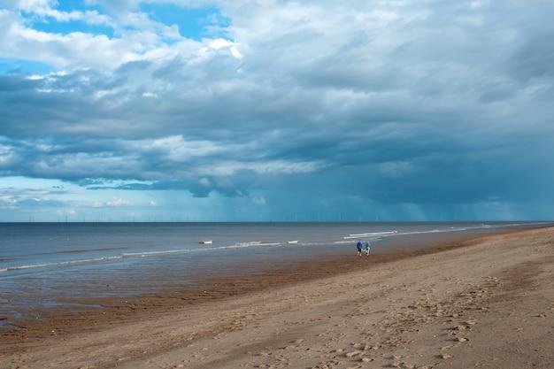 Песчаный пляж, море и пасмурное голубое небо в англии в солнечный день