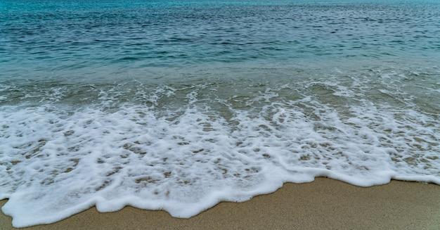 白い泡と青い海からの波と砂浜の海辺