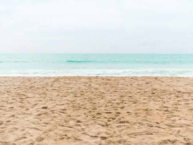 Песчаный пляж с размытым морем и небом для летнего отдыха.