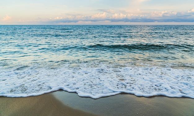 저녁에 푸른 바다에서 하얀 거품과 모래 해변