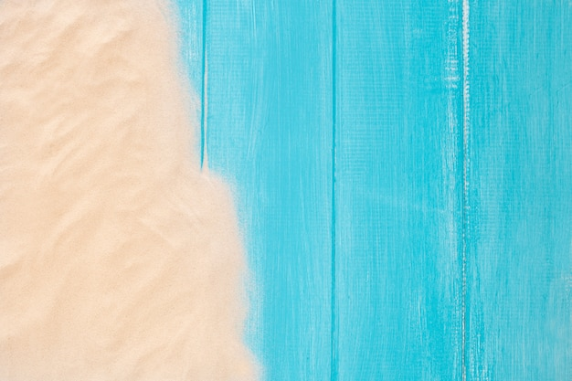 Sand border on blue wooden background with copy space