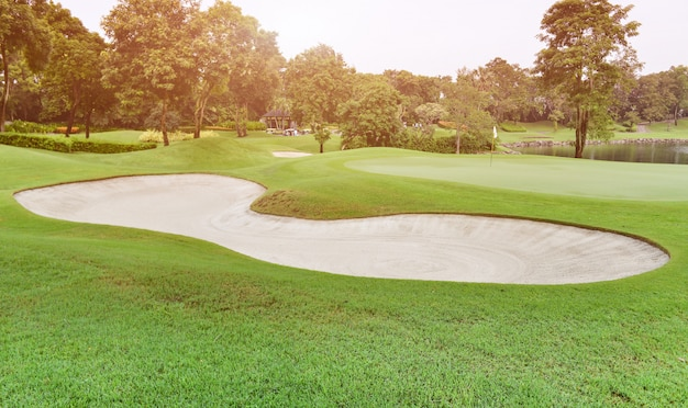 Sand bunker in green golf fairway.