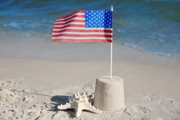 해변에 미국 국기와 모래 성