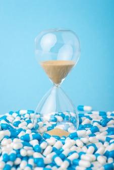 錠剤の山に砂時計