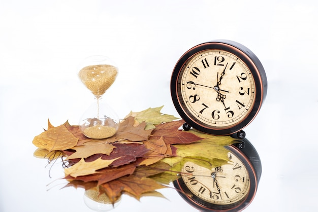 Sand clock and simple alarm clock on mirror table with autumn leaves.