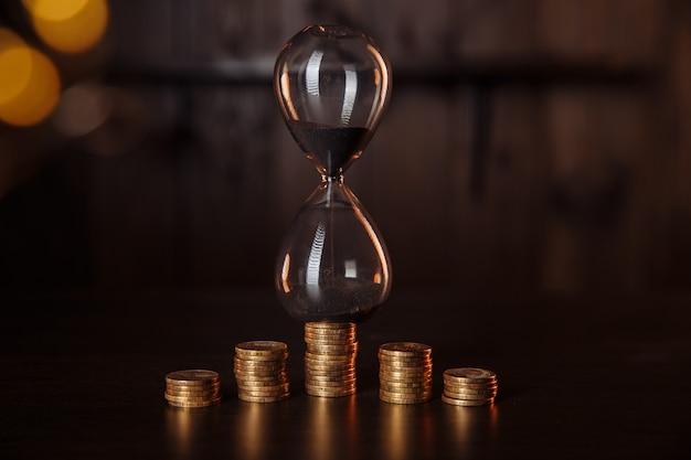 동전의 스택과 함께 모래 시계입니다. 시간은 돈, 투자 개념입니다.