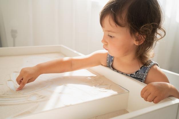 子供のための砂の製図台。小さな女の子が軽い砂のテーブルに指で描く