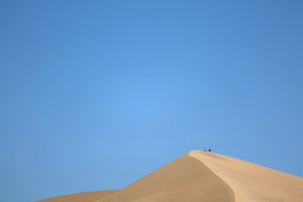 Sand dune of huacachina desert with people sitting on the top, ica region of peru