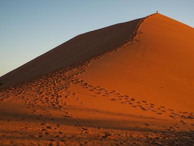 Sand dune ridge to summit with footprint in vast desert, sossus, namibia