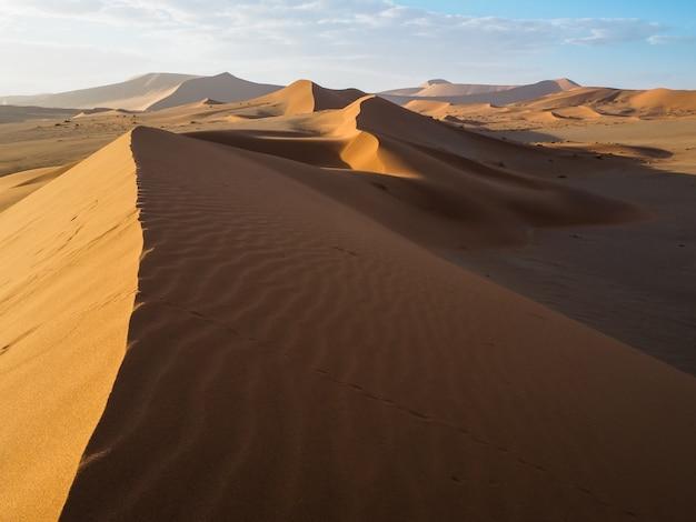 Sand dune ridge in vast orange brown desert landscape of hiddenvlei, sossus, namibia