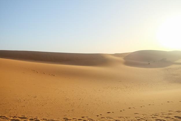 Sand dunes against clear blue sky background in sahara desert.