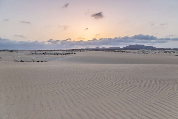 Sand, dunes and volcanic mountains at sunset landscape at the natural park of corralejo, fuerteventura, canary islands, spain.