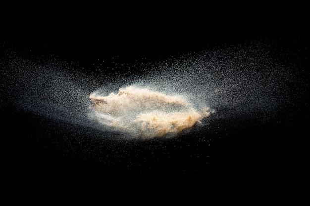 Взрыв песка, изолированные на черном фоне. заморозьте движение всплеска песчаной пыли.