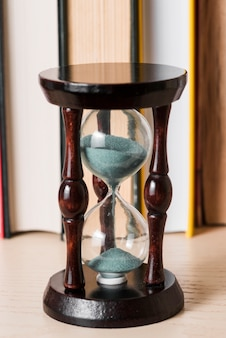 Sand falling in transparent hourglass on wooden desk