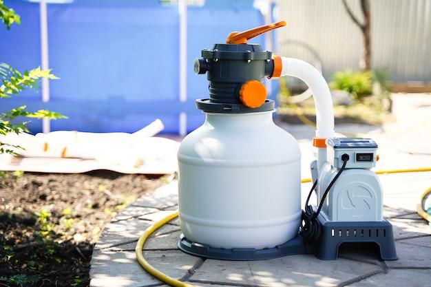 フレームポリエチレンプールの背景にあるプールの水を浄化するための砂ろ過システム