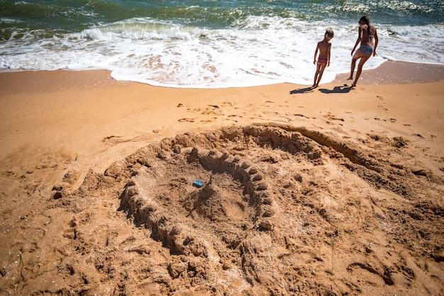 아이들이 지은 모래 요새는 화창한 따뜻한 여름날 해변에서 시끄러운 바다 파도 옆에 서있는 두 어린 소녀 사이에 서 있습니다.