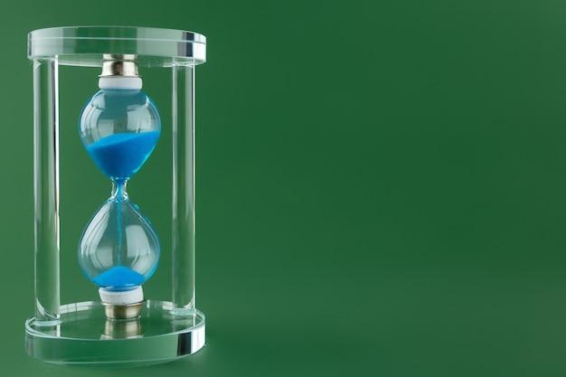 Sand hourglass on dark green paper