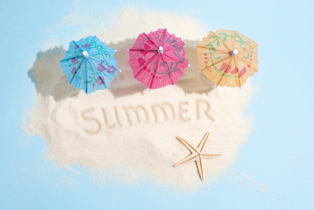 Sand island with three colorful umbrellas and starfish on a blue background, top view, summer sea vacation concept, close up.