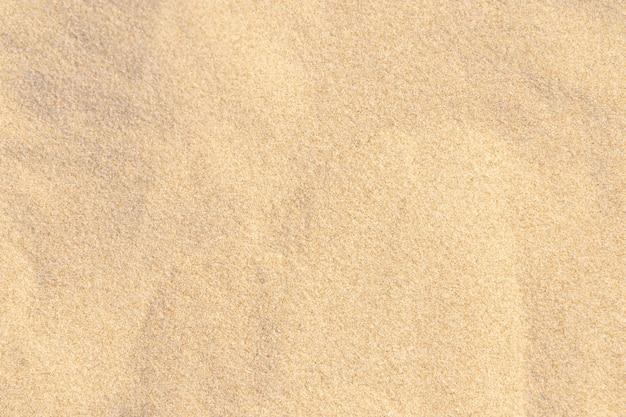背景の砂模様のテクスチャ。熱帯のビーチからの茶色の砂漠のパターン。閉じる。