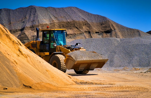 Sand quarry, excavating equipment, bulldozer with heap of sand and gravel