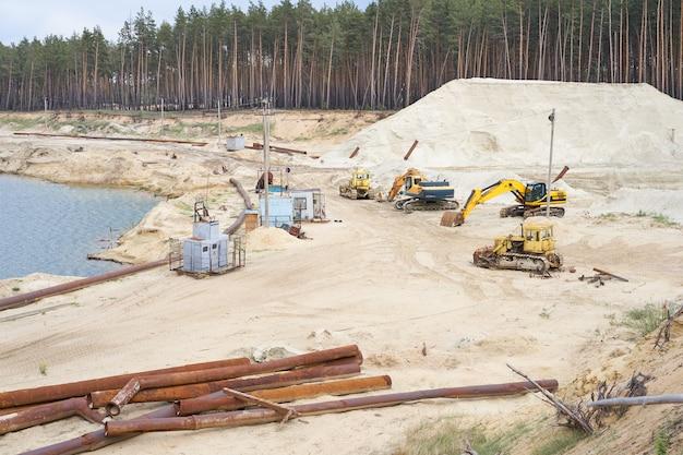 모래 채석장 광산 산업 장비 굴삭기 트랙터 호수 물 근처에 서있는 모래 땅