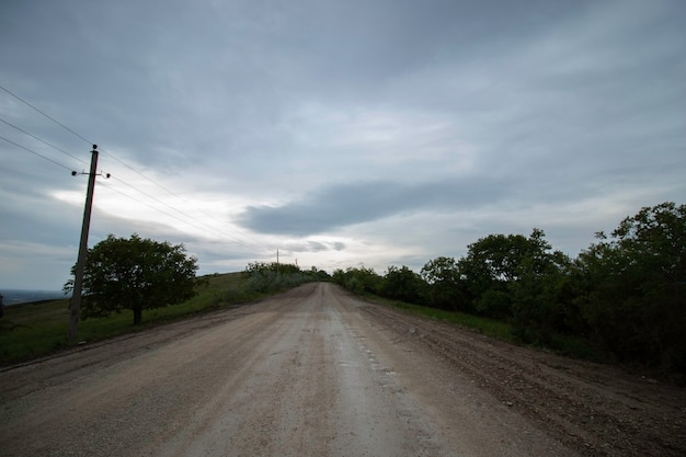Sand road to the clouds white sandy road to the cloudy sky and green grass on the side