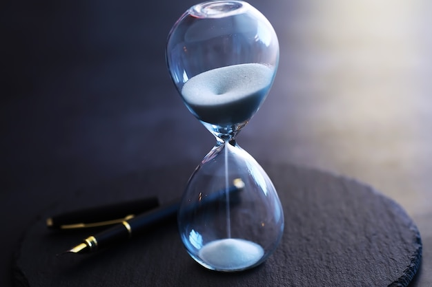 Sand running through the bulbs of an hourglass measuring the passing time in a countdown to a deadline, on a dark table background with copy space.