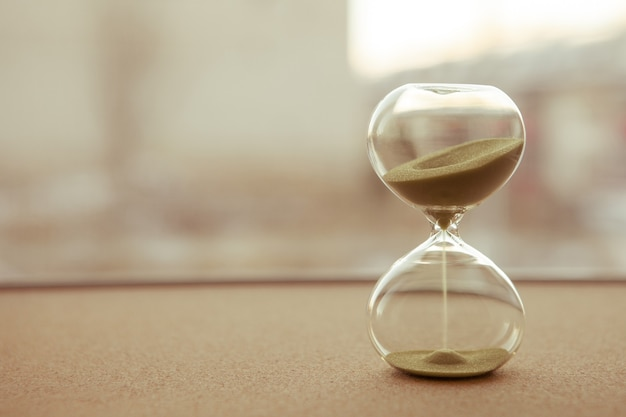 Sand running through the bulbs of an hourglass measuring the passing time in a countdown to a deadline