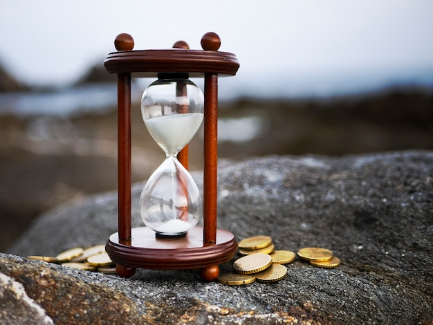 Sand running through the shape of hourglass with coins on rock background. time investment and retirement saving.