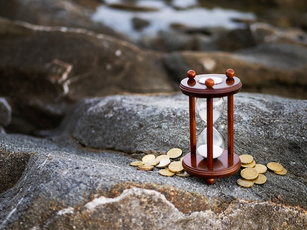 Sand running through the shape of hourglass with coins on rock background.