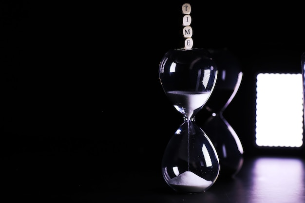 Песок пробегает по лампочкам песочных часов, измеряя время в обратном отсчете до крайнего срока, на темном фоне стола с местом для копирования.