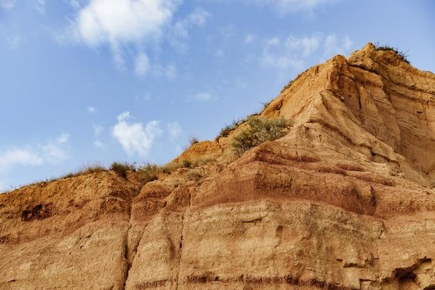 푸른 하늘을 배경으로 모래 돌과 바위 절벽