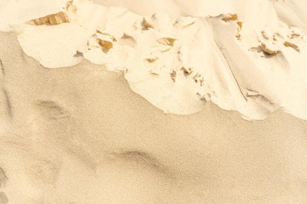砂のテクスチャの背景。熱帯のビーチからの茶色の砂漠のパターン。閉じる。
