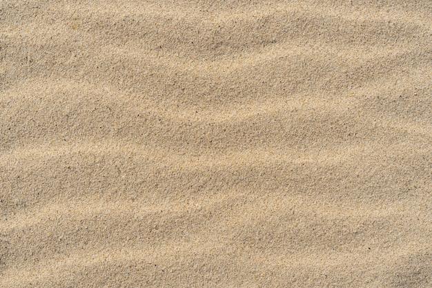 砂のテクスチャ。上面図。背景の砂浜。波線。