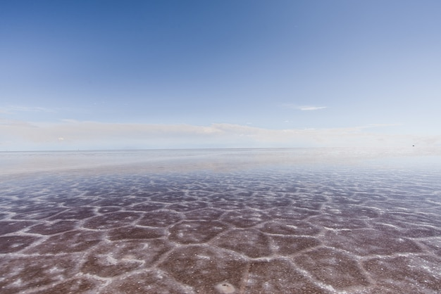 Sand texture visible under the crystal clear sea and the sky