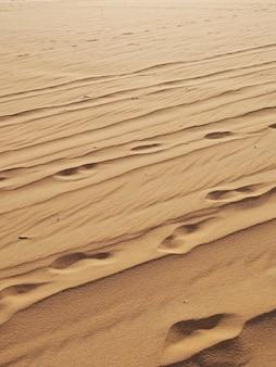 足跡の背景を持つ砂のテクスチャです。