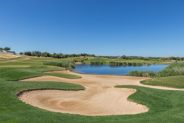 Песколовка на поле для гольфа с озером.