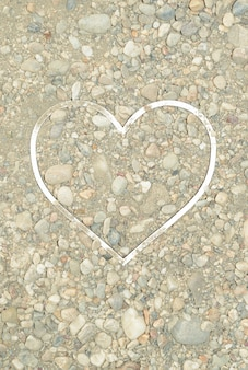 Sand with stones in which a white heart shaped frame is placed. summer concept of beach and love