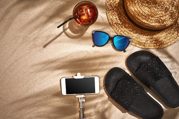 샌들 밀짚 모자와 선글라스는 모래 배경 꼭대기에서 볼 수 있습니다.