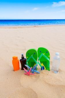 바다 쪽 모래 사장에 샌들과 생수 및 선탠 크림 병
