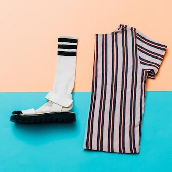 サンダルと靴下。 tシャツ。トレンドのストリップ。夏のミニマルクリエイティブ。流行に敏感なスタイルの上面図