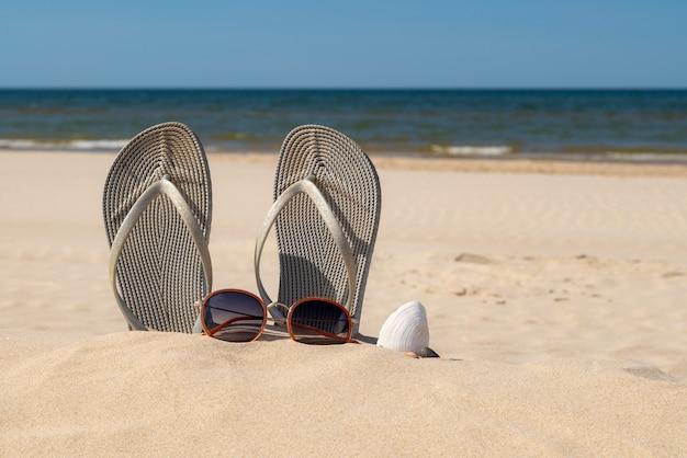 美しい晴れた日のビーチでのサンダルとサングラス