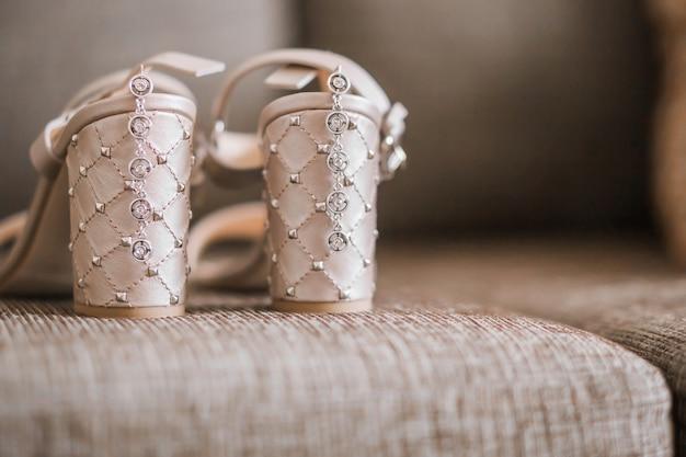 花嫁のアクセサリーとしてのサンダルまたはかかとの高い靴とイヤリング。横の写真