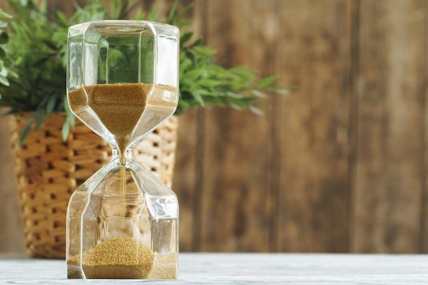 木製bakgroundの砂時計。時間の概念