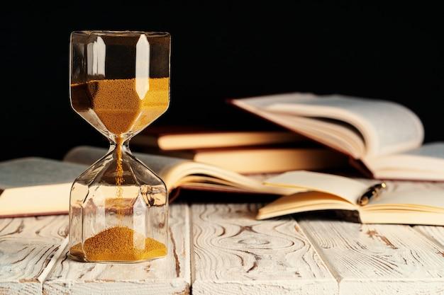열린 책 나무 테이블에 모래 시계를 닫습니다.