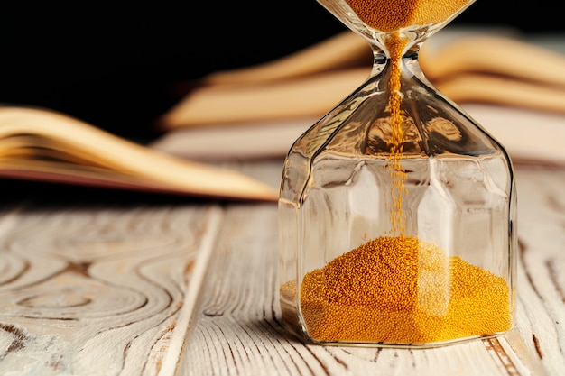 開かれた本の木製テーブルの上の砂時計をクローズアップ
