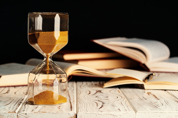 Sandglass on wooden table with opened book close up